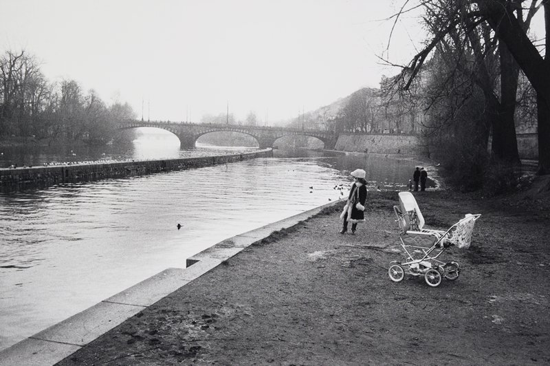 black and white photo of little girl looking at river with pram in foreground