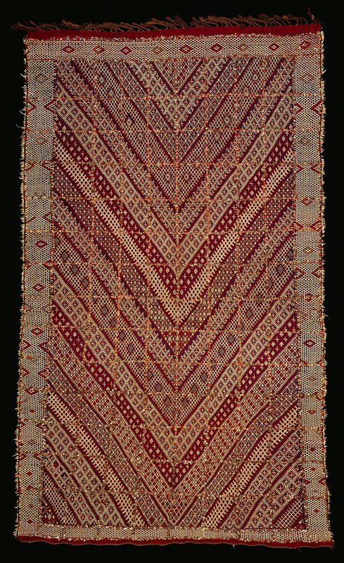 woven, blanket-like object with pile created with multicolored threads on back; chevrons on front, each woven in different pattern with white, blue, red, orange and tan yarn on maroon ground; rows of sequins sewn on top in a grid; twisted brown fringe on one short end