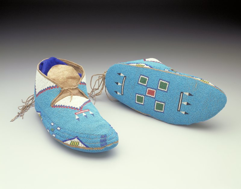 beaded overall, including soles; blue beaded ground with triangles and squares in white, red, dark blue, green, yellow and black; fringe at heel, plain tongue; tie at front