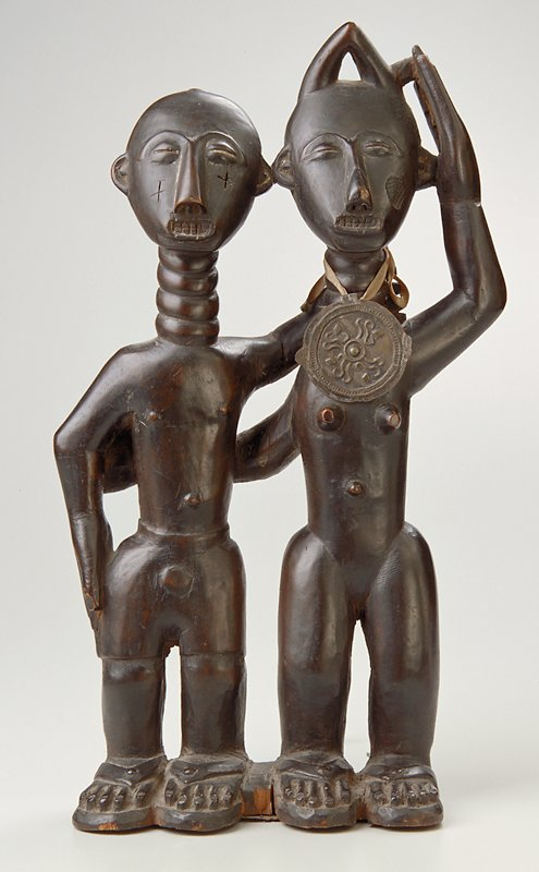standing male and female couple, facing forward; man on L wears short pants and has linear scarifications on checks, with PL hand on woman's neck; woman at R wears a 'soul wishes' medallion hanging from a ribbon around her neck; woman has PL hand next to her head and PR arm around man's waist; both figures wear sandals and rings around their necks