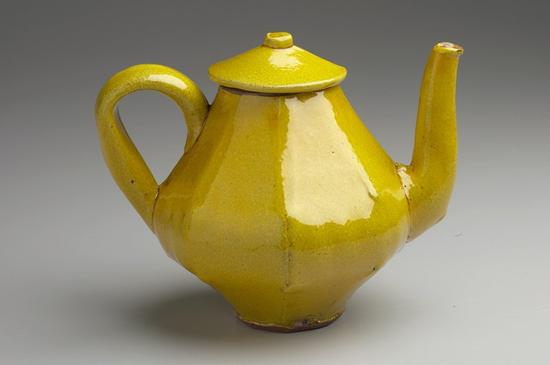 yellow glaze; 8 flat facets on bulbous body; thick applied handle; tall spout; small cylindrical knob on lid