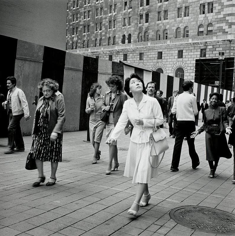 people walking on a city sidewalk in front of a striped plywood wall; woman in front wearing pleated skirt, looking up