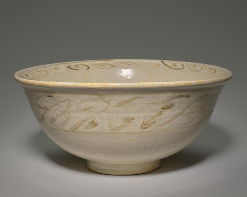 deep white-glazed bowl on a medium foot; interior rim and band on exterior decorated with swirls in greenish-brown; interior bottom decorated with brown and green foliate forms