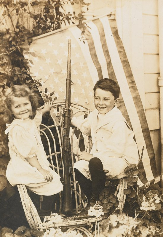 small boy and girl seated on opposite arms of a bentwood chair; boy holds a rifle resting on chair seat; American flag behind children
