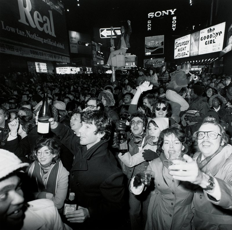 """large crowd on city street at night; woman with a horn sitting on a man's shoulders at R; man sitting on top of a """"DON'T WALK"""" signal at center"""