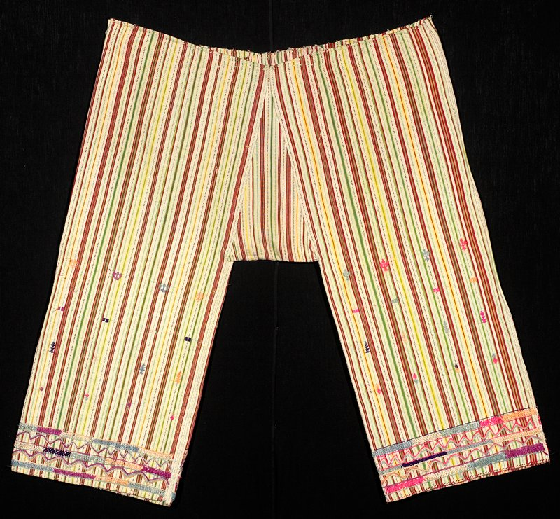 weft stripes in red, green and yellow on natural ecru ground; embroidered at cuffs in pinks, blue and purple; small embroidered geometric forms on legs