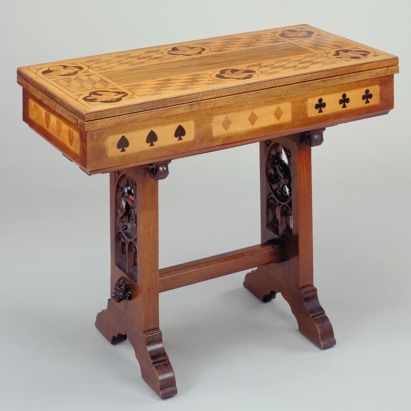 Tabletop unfolds like a book along one long side and pivots 90 degrees to form felt-topped gaming surface; decorated with six inlaid birds on corners and edges of tabletop with slanted checkerboards between; inlaid hearts, diamonds and clubs around apron; trestle base with lion and lion's head on each of two legs