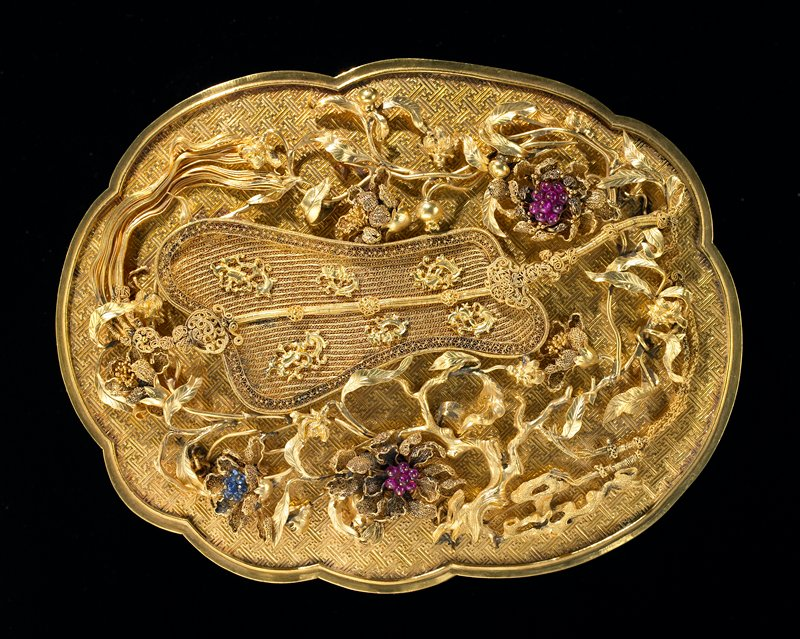 Gold presentation box; surface chased with swastika-fret design. Bears fan, emblem of Chung-Li Chuan, surrounded by delicately spun gold blossoms picked out with small cabochon rubies, saphires and green jade. One of a set of 8 presented to Emporor Ch'ien Lung in the 43rd year of his reign.