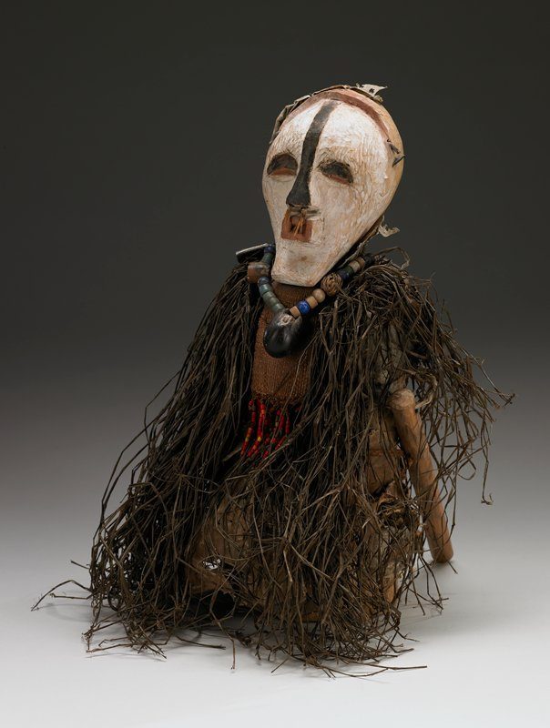 wood body with hanging dowel arms; elongated black and white face with hair in nostrils; wearing a beaded necklace; fiber breast plate trimmed in beads