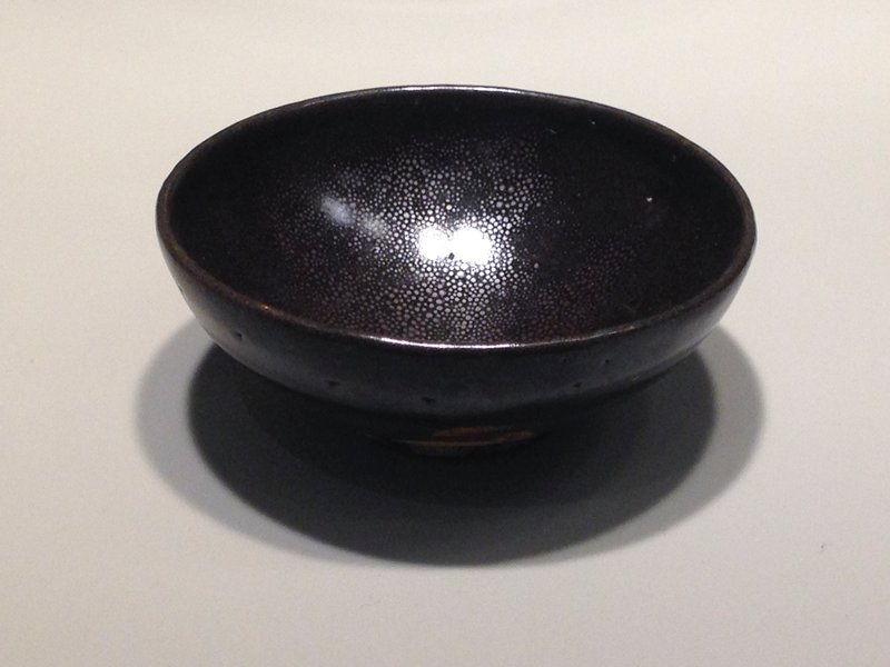 blackware, oil-spot glaze; small foot, straight lip; 2 layers of dark brown glaze, with silvery spotting on interior; unglazed bottom portion