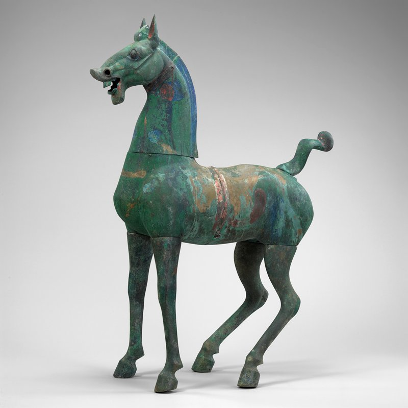 standing horse with legs slightly splayed outward; wide eyes; open mouth with exposed teeth; upward-pointed ears; green patina with white, blue and red pigment traces