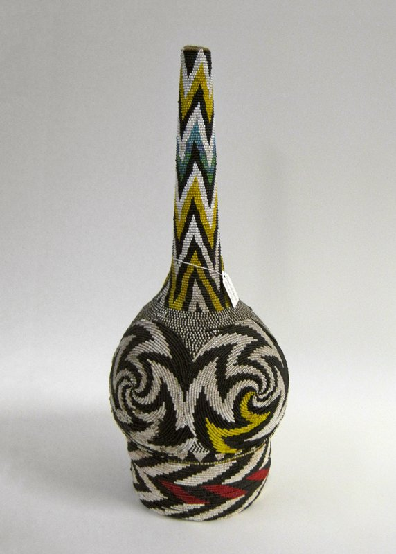 rounded body on tall, thick base; long, thin neck; beaded overall with primarily black and white designs, with red, yellow, blue and green accents; zigzag patterns on base and neck; circles with zigzags on body