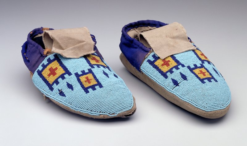 hide soles; canvas uppers; blue and brown cloth collar around ankles; vamps beaded with dark blue, red and yellow geometric deisngs on light blue ground
