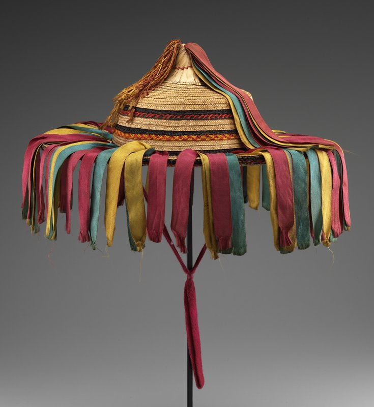 brimmed straw hat with conical top; clusters of red, green, and yellow ribbons hang over brim and from top; red and yellow silk tassel on top. Textile - Non-Woven