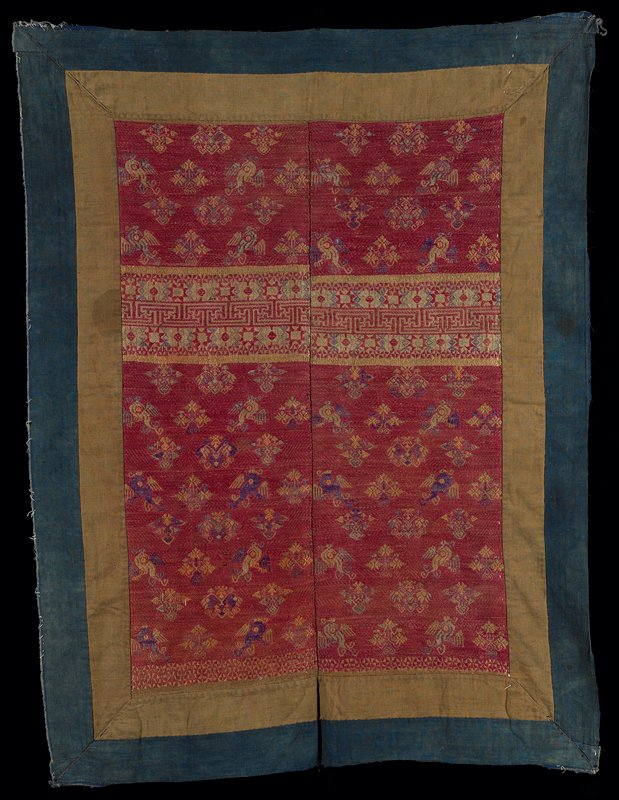 outer blue border; inner brown border; two central panels sewn together; central panels are predominately magenta with bird and flower forms and geometric bands at center and one end