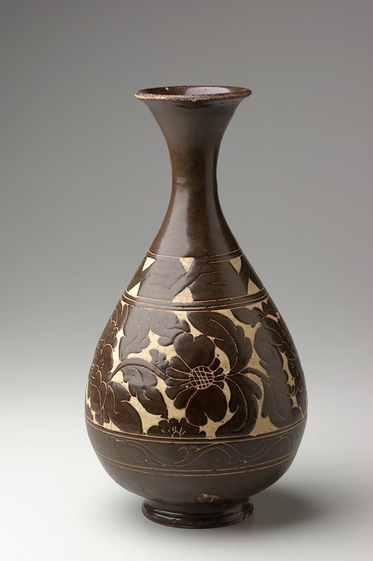 rounded body with thin tapering neck, flaring to wide lip; dark brown glaze with 2 bands with cut-glaze decoration with floral motifs