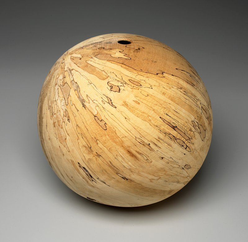 """light-colored wood sphere, with brown striations; round hole near one end; unfinished surface; very small flat """"base"""""""