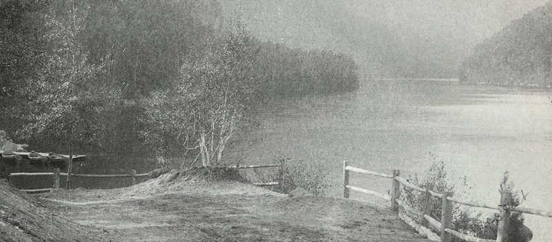 wood fence in foreground at the edge of a body of water; 3 docked rowboats at L