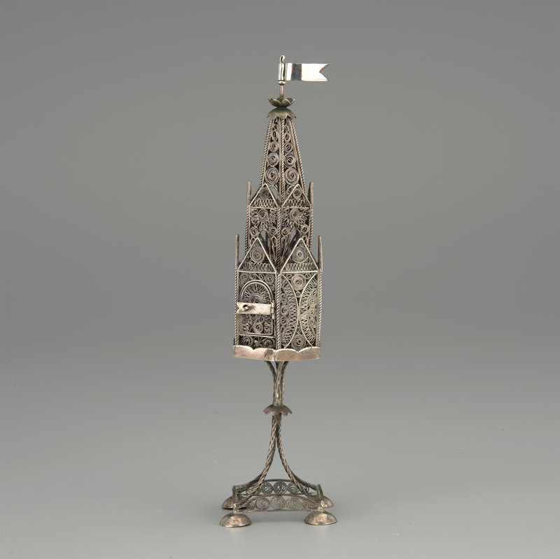 architectural box with 4 domed feet attached to 4-pronged stem; silver openwork filigree overall; movable flag at top