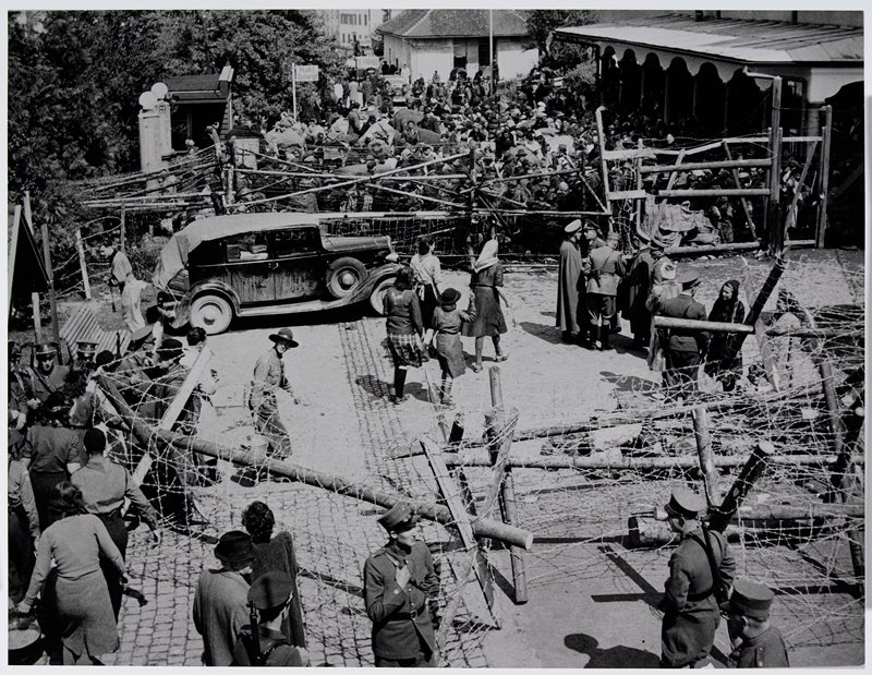 crowds of people on street in background; blockades of logs and barbed wire in foreground; groups of soldiers and women in foreground