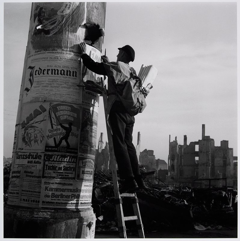 man on a ladder hanging a poster on a column with other bills; ruins in background