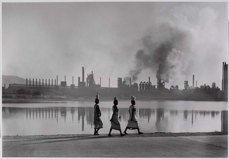 3 figures, each balancing a small parcel on head, walking next to a lake with a factory on the opposite shore