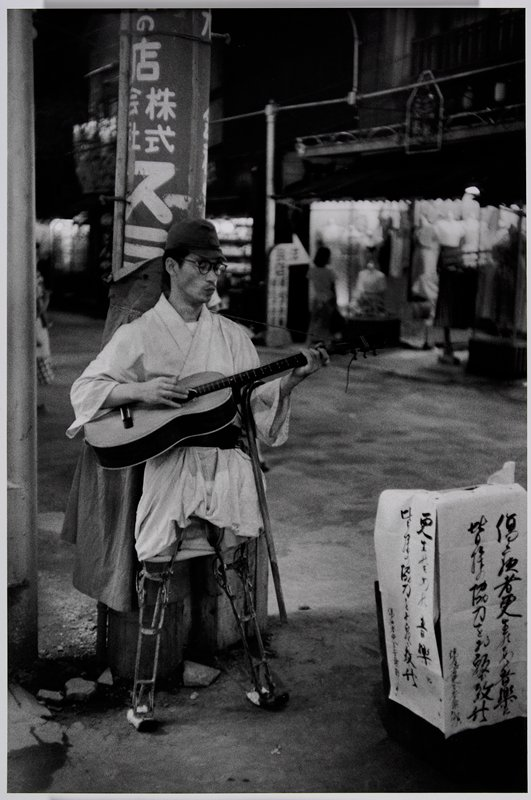 standing man with 2 artifical metal legs, wearing glasses, kimono and cap, strumming a guitar; can hooked over PL arm