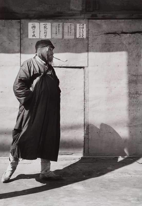 standing bearded man wearing a cap with ear flaps, coat and boots, smoking a pipe
