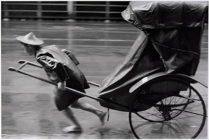 blurry image of barefoot man wearing a straw hat and a raincoat pulling a tarp-covered rickshaw