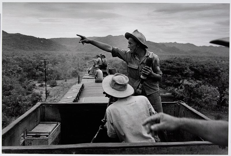 standing man on top of a train, smoking and holding an explosive in his PL hand and pointing with his PR hand; back of a seated man in front of him; other men on top of train cars in background