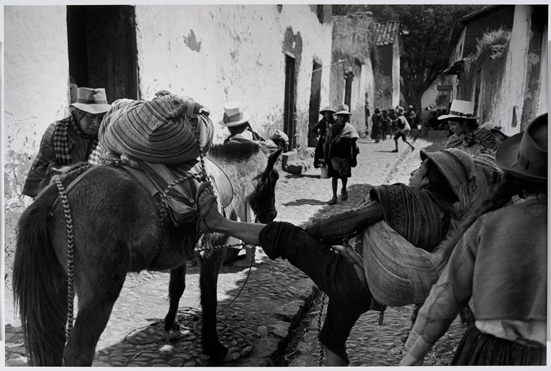 man bracing his foot against the saddle on a horse while pulling on a rope to attach a bundle to the saddle; narrow street between buildings, with other figures throughout