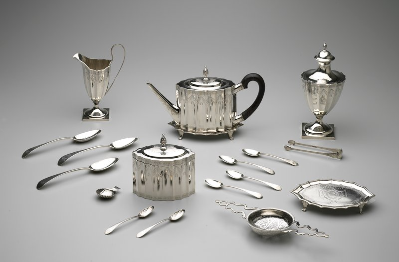 tea service, Federal Style, consisting of teapot and lid, stand for teapot, tea caddy with hinged lid, fitted with lock and key, stand for teacaddy, covered sugar urn, cream pitcher, shell-shaped tea scoop, tea or punch strainer, pair of sugar tongs with shell-shaped ends; fluted design with engraved and pricked swags and medallions containing the monogram of John and Mehitable Templeman and all bearing Revere hall mark; teaspoons