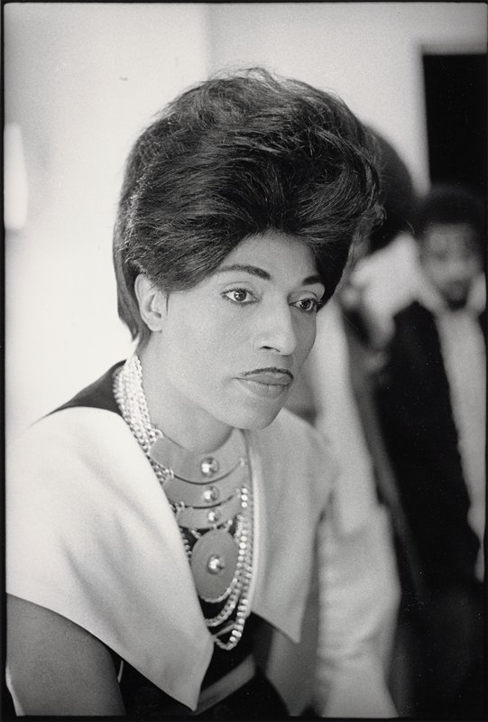 Little Richard, with tall pompador hairstyle, wearing chains and 4 medallions around his neck and wide white collar
