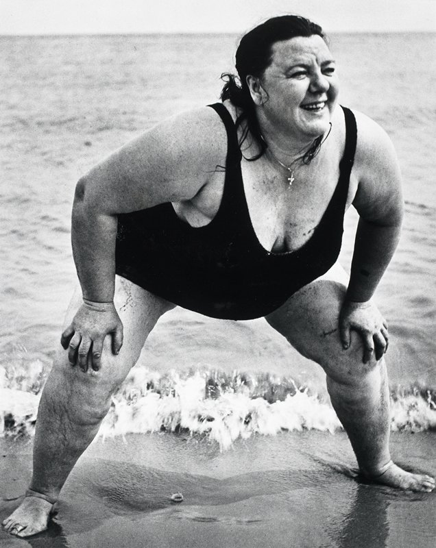 large dark-haired woman in a black one-piece bathing suit; woman has her hands on her knees and is smiling; standing on sand at water's edge