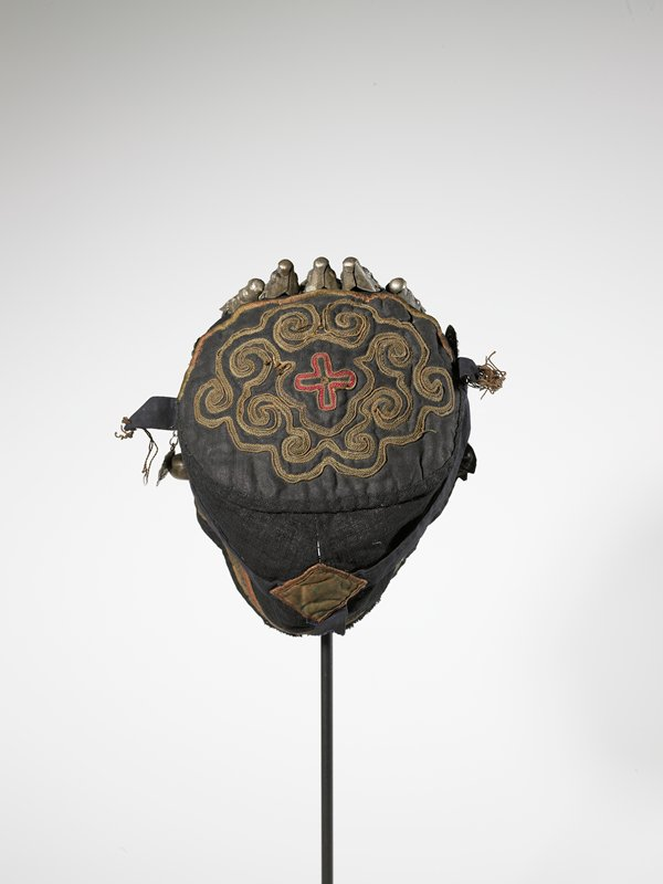 black hat with brown and red organic and geometric embroidery on crown; eight silver figures and eight half-spheres attached to front; medallion at each temple with two pendants on chains (fish and bell)
