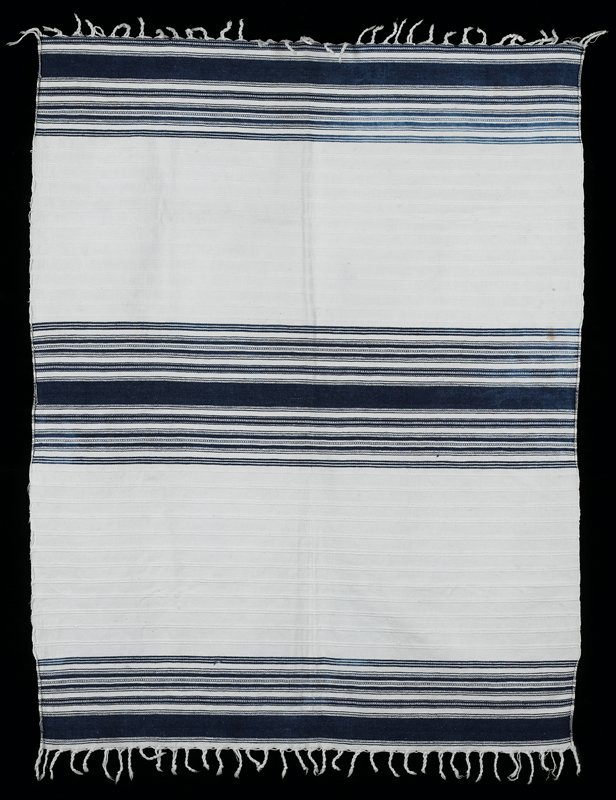 White background with blue weft striped sections on both ends and in the center; white twisted warp fringe on both ends.