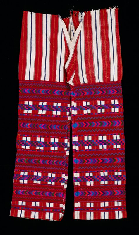 Red and white vertical striped four panel pants, stripes in orange and green; chevron and arrow designs in red supplementary weft patterning; border of square checks.