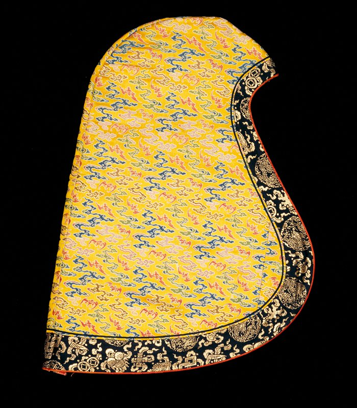 Priest's cowl of imperial yellow satin brocade with all-over design of bats and loose cloud forms in shades of blue, green, pink, red, brown, and mauve. Wide band of black and gold brocade aroung border. Narrow binding of rust-red satin. Lining of faded crimson figured silk.