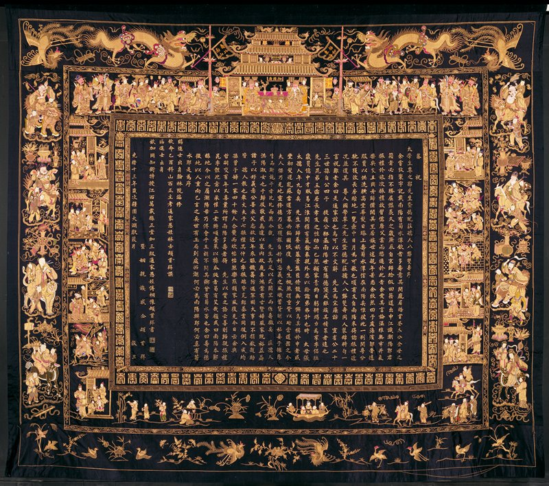 Hanging, large, of embroidered blue black satin. Central panel contains a long inscription. In the wide border figures of the Eight Immortals, cranes, bats and various symbols in couched gold thread and colors. A birthday hanging presented to a couple on their 80th birthday. Lining of coarse blue cotton. Former Classification: Textiles - Tapestry