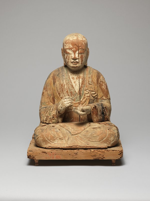 Buddha seated with legs folded and feet over knees; PR hand held in loose fist; PL hand open, gently cradling round object; fragments of white and green pigment; sits on flat base with pigment fragments