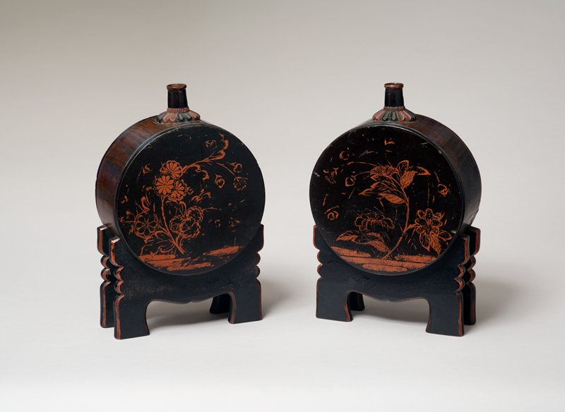 one of two sake containers in the shape of a large drum with attached supports shaped like drum-stands; painted chrysanthemums and other flowering plants; base of spout shaped like chrysanthemum