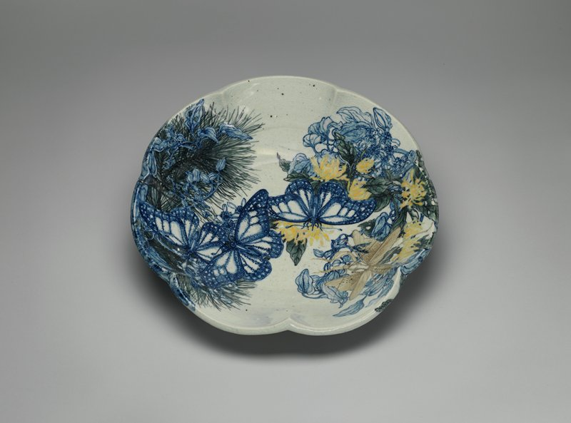 bowl with scalloped edges; underglaze design of blue butterflies with blue flowers against green pine boughs; yellow chrysanthemum blossoms, blue flowers and foliage; tan grasshopper