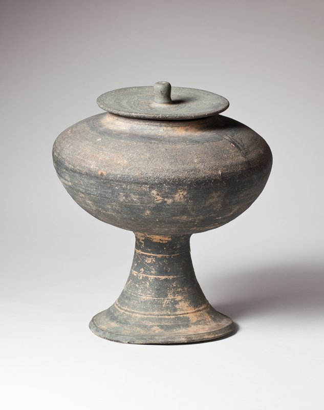 round bowl with slightly raised lip; wide shoulder; elevated on short, conical stand with concentric incised lines; grayish coloring with brown areas; small flat lid with short knob; slightly lopsided