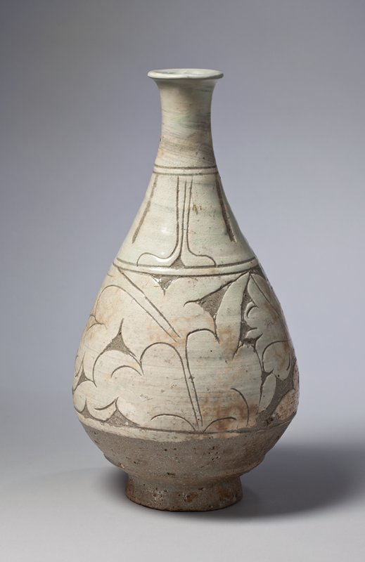 light green and tan bottle with grey recessed areas; pear-shaped; round foot; raised, billowing, floral leaf patterns
