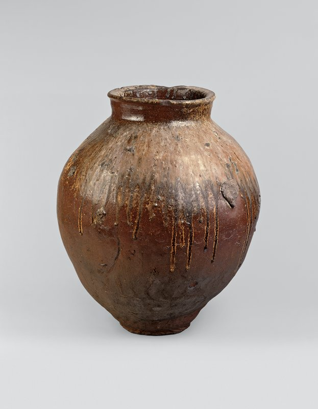 very large dark brown jar with irregular, bulbous shape; short neck, rounded lip; tan, beige, and gray drip glaze top one-third of body; drips down mouth interior; large stoneware globules on sides