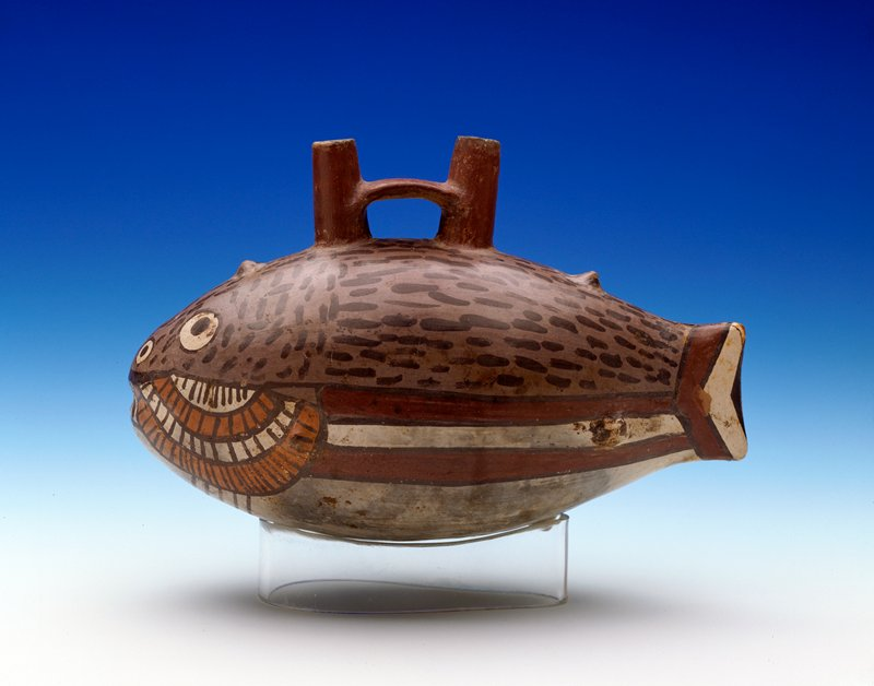 Pot in form of Fish with a double spout handle rising from the back. Slight modelling on head, tail, and fin area. Other features painted in grey, black, yellow, red and white. Broken at tail; cracked around head.