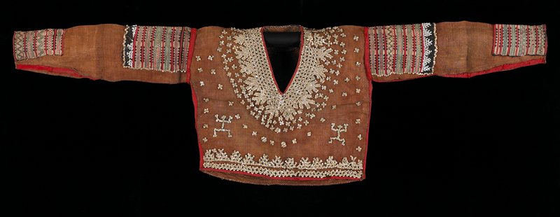 Tan, front and back, decorated with pearls; at shoulders and cuffs appliqué pieces sewn, red ribbon sewn at edge.