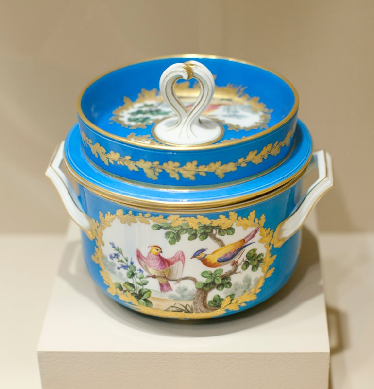 ice pail with removable bowl inside; on the blue ground of body and cover are medallions reserved in white and wreathed in gold, painted with birds in a landscape; the twisted handle of the lid is covered with gold lines and a row of gold leaves encircles the deep outer ridge of the cover; the body of the bowl rests on three, bun-shaped feet; ice was placed between the body and the liner and inside the lid to keep ice cream cold inside