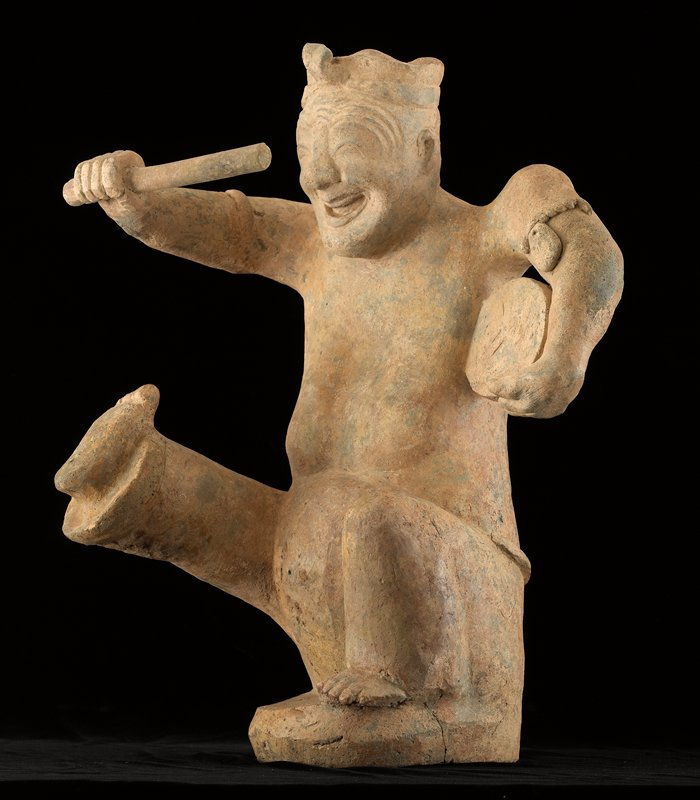smiling, animated figure with open mouth, closed eyes and wrinkled brow; PL knee bent; PR leg extended; bare feet; PR arm extended, holding a drum beater; drum in crook of PL arm, next to body