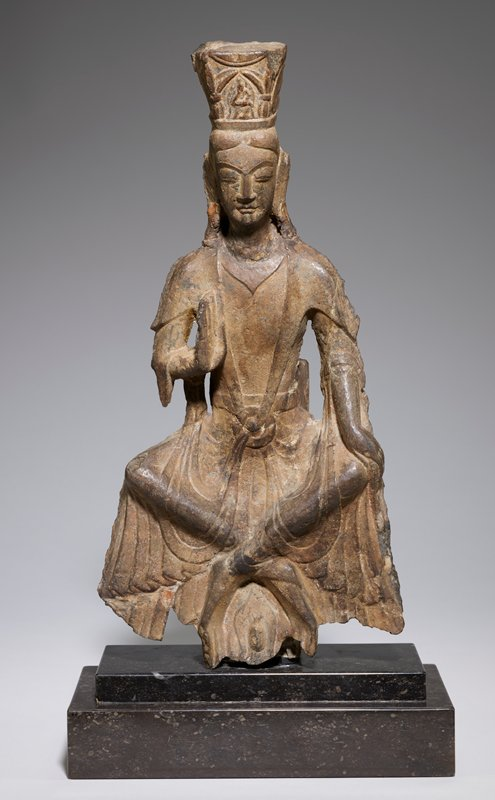 Figure of a Maitreya Buddha, porbably Avalokitesvara, seated as if on a stool, his legs crossed at the ankles, his body slightly bent forward, and his hands in the 'do not fear' attitude. The upper part of the body is partially covered with a scarf which falls over the upper arms in pointed cap sleeves and merges with the skirt drapery. The ribbon-like ends of the scarf are knotted in an x-form over the abdomen. The skirt hangs in flaring, rippled pleats over the legs, which are clearly visible under the drapery. The face is typical of the Wei style of Lung Men, with lips and nose firmly modelled, eyebrows falling to meet the lines of the nose, eyes set low beneath the brows, and lids cut in a narrow almond. The hair is parted in the center, and crowned with a square tiara with a figure of Amitabha in front. This figure comes from the Ping Yang cave at Lung Men.